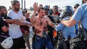 Los manifestantes entregan a la Policía al conductor del camión que trató de arrollar a la multitud, en Minneápolis.