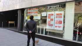 Un hombre pasa con su perro frente a una oficina de Empleo de Madrid.