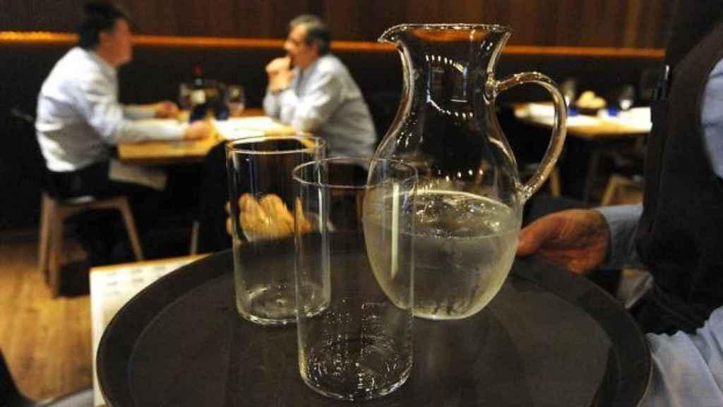 Un camarero con vasos de agua.
