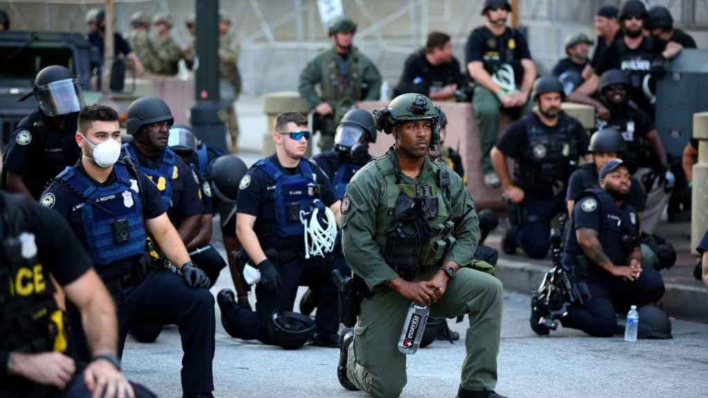 Oficiales se arrodillan con los manifestantes durante una protesta en Atlanta.