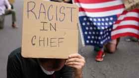Un manifestante frente a la Casa Blanca con un cartel que dice Racista en Jefe en referencia a Donald Trump.