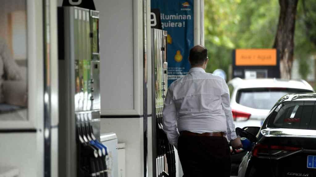 Un hombre echa gasolina a su coche en una gasolinera.