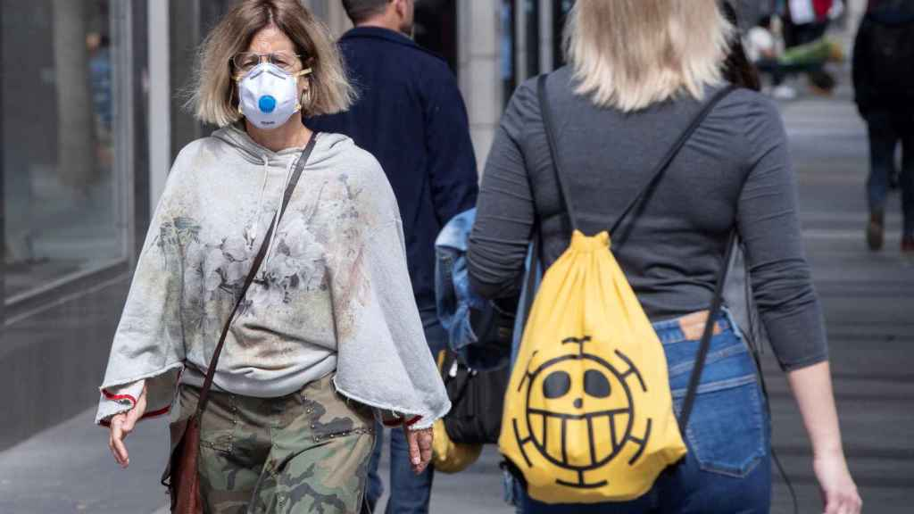 Una mujer paseando con mascarilla por la calle.