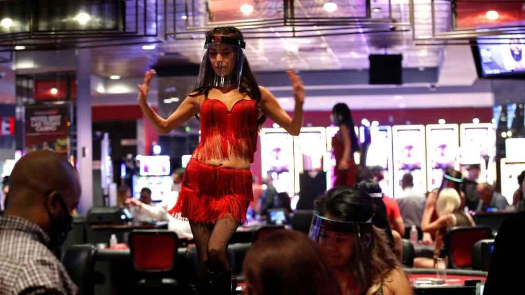 Una mujer baila detrás de una mesa de juego llevando una pantalla protectora.