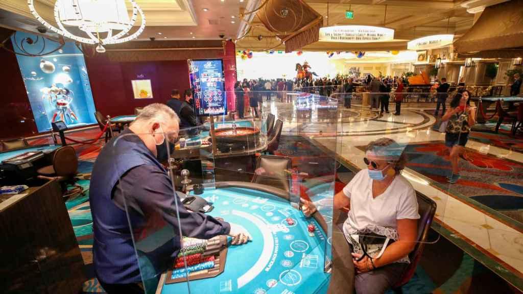 Una mujer juega al blackjack con una mampara que la separa del crupier en el Hotel-Casino Bellagio.