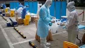 Médicos chinos quitándose los equipos de protección individual.