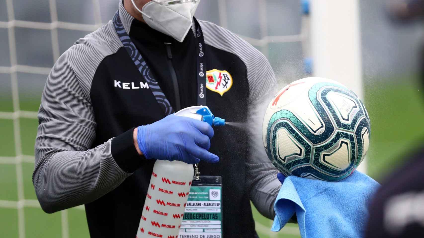 Uno de los recogepelotas del Rayo desinfectando un balón