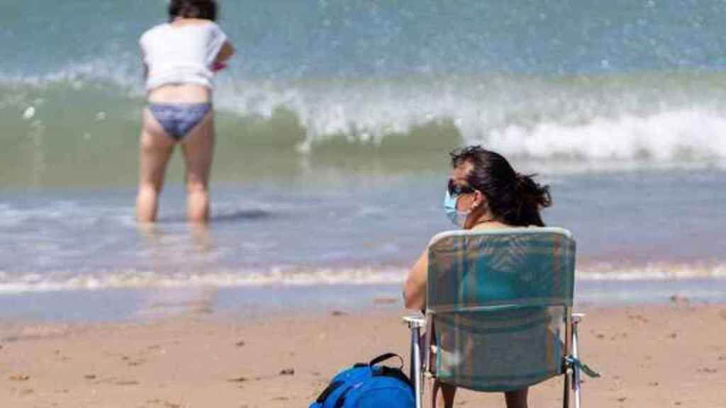 Una mujer con mascarilla en una playa de Andalucía, en una imagen de archivo.