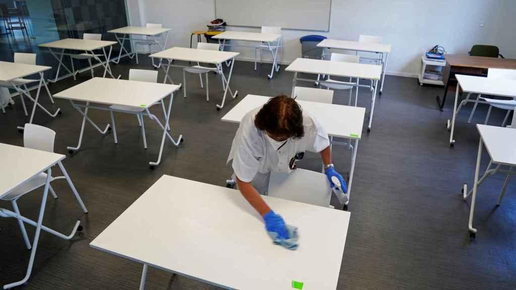 Limpian las mesas antes de que lleguen los alumnos de un colegio de San Sebastián.