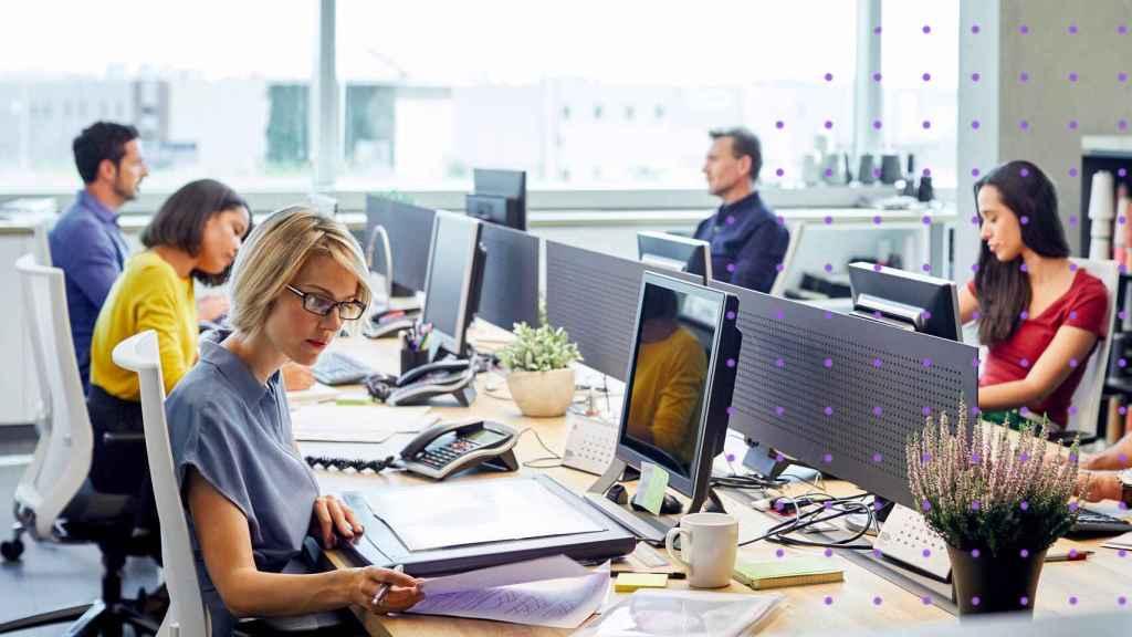 Varios trabajadores en su puesto de trabajo.