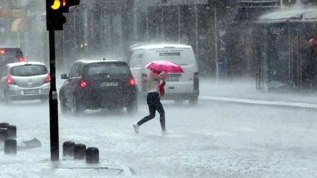 Una mujer cruza la calle bajo una lluvia torrencial. Efe/Epa Fehim Demir