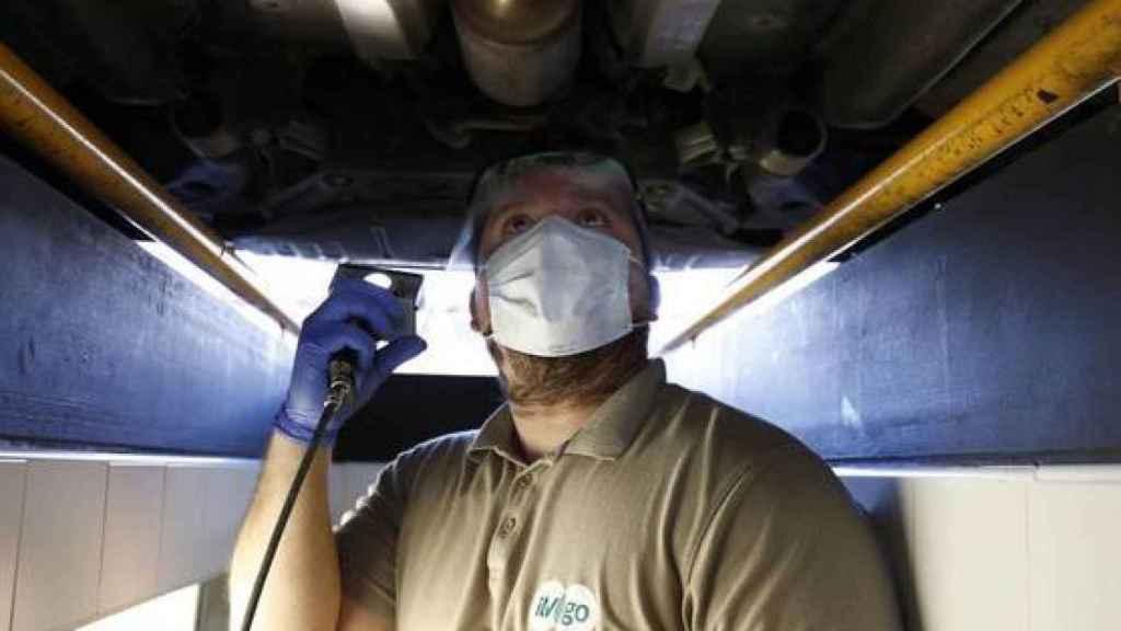 Un operario revisa un coche en la ITV con mascarilla.