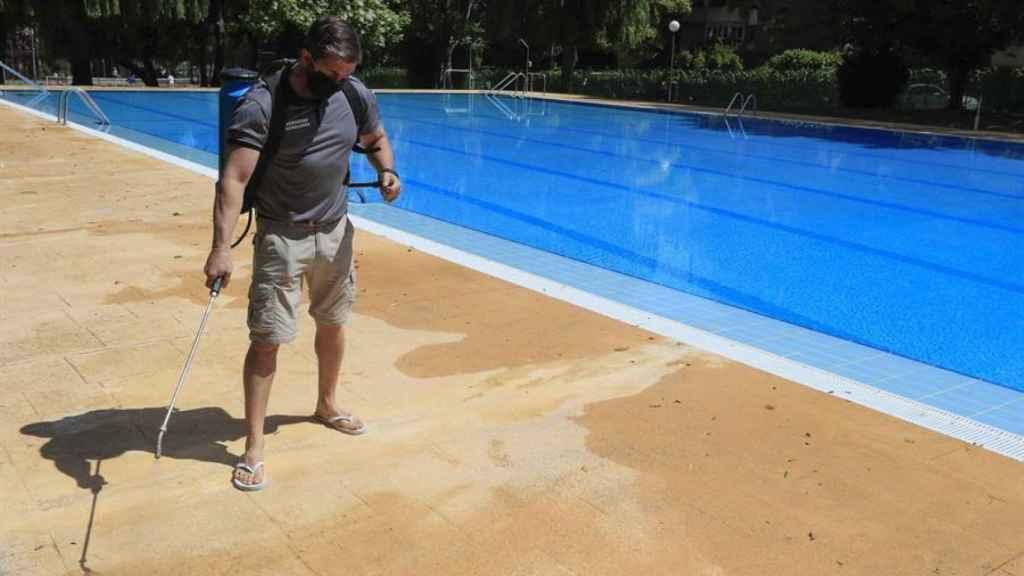 Un operario desinfecta una piscina.