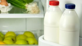 Unas botellas de leche en la puerta de la nevera