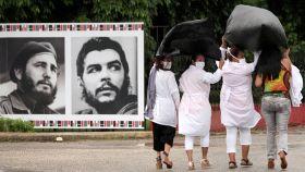 Unas médicas pasan junto a unas fotografías de Fidel Castro y el Che Guevara en la Havana.