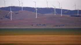 FILE PHOTO: A fence is seen in front of wind turbines that are part of the Infigen Energy Capital Wind Farm located on the hills surrounding Lake George, near the Australian capital city of Canberra