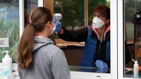 Una mujer toma la temperatura a otra en Alemania. Reuters.