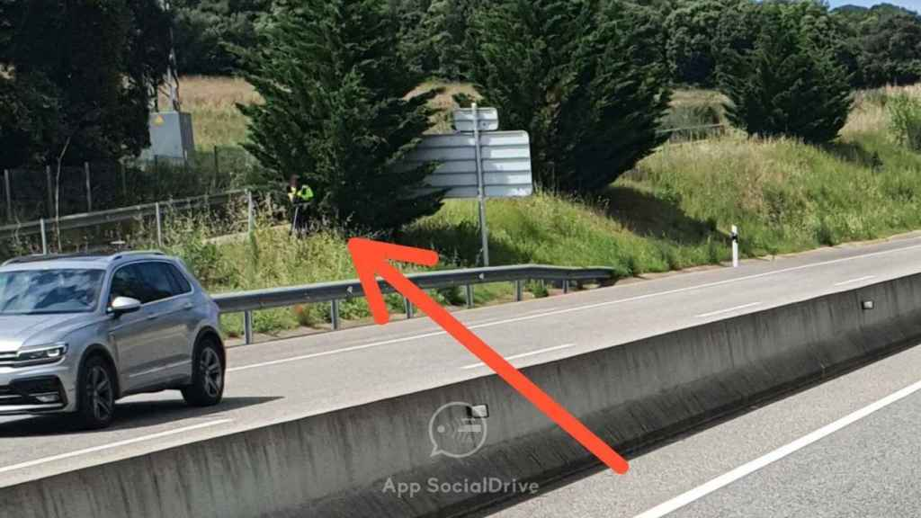 Un agente escondido tras un árbol con lo que parece un radar láser.