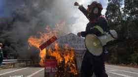 Un trabajador del comité de empresa de Alcoa levanta el brazo como signo de protesta en la concentración realizada en la A8.