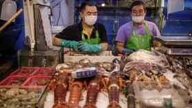 Vendedores de pescado con mascarilla en un mercado de Pekín