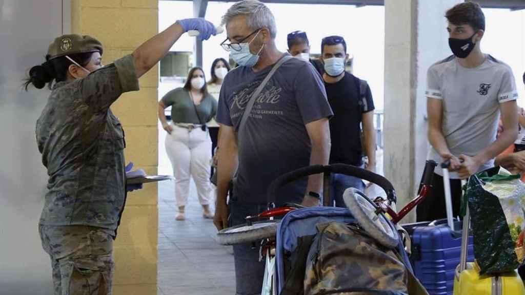 Una enfermera del Ejército toma la temperatura a varios pasajeros.