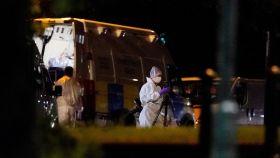 Trabajadores forenses trabajan en la escena del crimen.