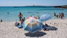 Varias personas este domingo en el primer día de la nueva normalidad en la playa de Punta Prima, Menorca.
