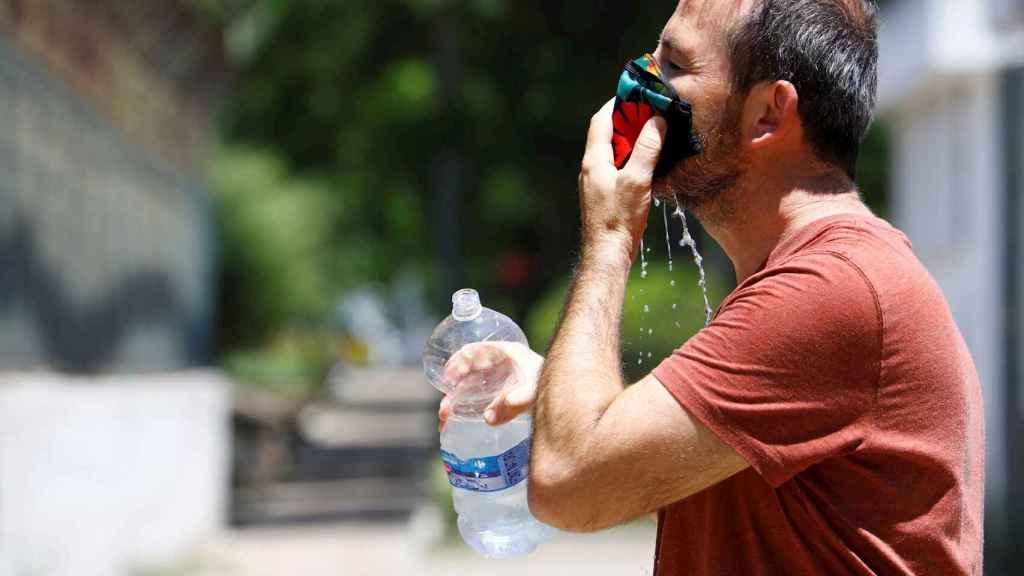 Un joven refrescándose la mascarilla contra el calor en Córdoba. EFE/Salas.