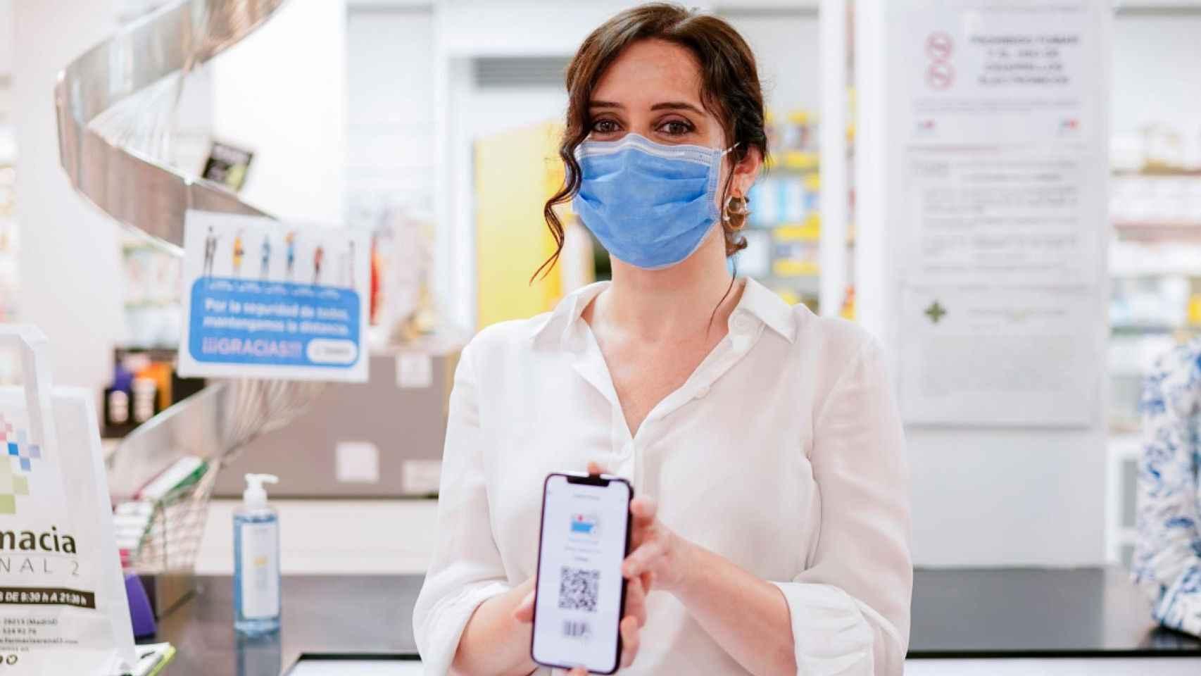 Isabel Díaz Ayuso con la Tarjeta Sanitaria Virtual en su móvil.