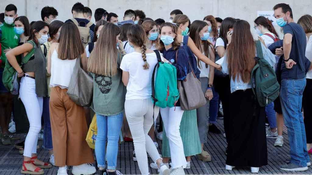 Varios alumnos, con mascarilla, se agolpan a la entrada de la Universidad.