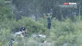 Un Guardia Civil indicando a un espectador en el monte cercano al Camilo Cano que no puede estar ahí