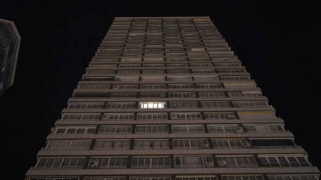 Una sola luz encendida en una torre de apartamentos a pie de playa, en Benidorm.