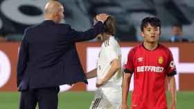 Zinedine Zidane felicita a Luka Modric por su partido mientras pasa al lado Take Kubo