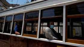 Viajeros con mascarilla en un tranvía de Lisboa.