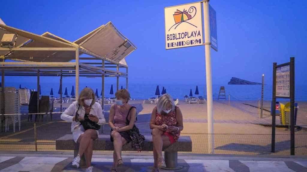 Tres personas con mascarillas sentadas frente a la playa de Benidorm.