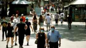 Paseantes por Las Ramblas de Barcelona con mascarilla. EFE/Toni Albir