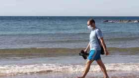 Una persona pasea por la playa con mascarilla. Efe