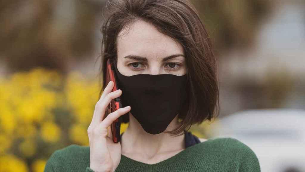 Mujer con mascarilla usa un móvil.