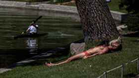 Un hombre hace deporte en una piragua mientras otro toma el sol en el lago de la Casa de Campo en Madrid este martes.