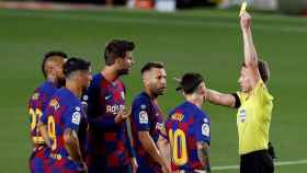 Hernández Hernández enseña la tarjeta amarilla a Gerard Piqué por las protestas en el Barcelona - Atlético de Madrid