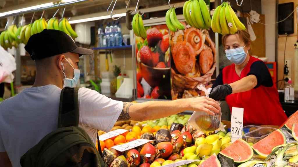 Una trabajadora de una frutería atendiendo a un cliente.
