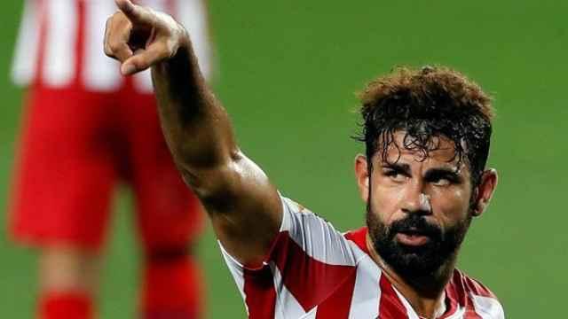 Diego Costa señala a sus compañeros y el banquillo en el Camp Nou