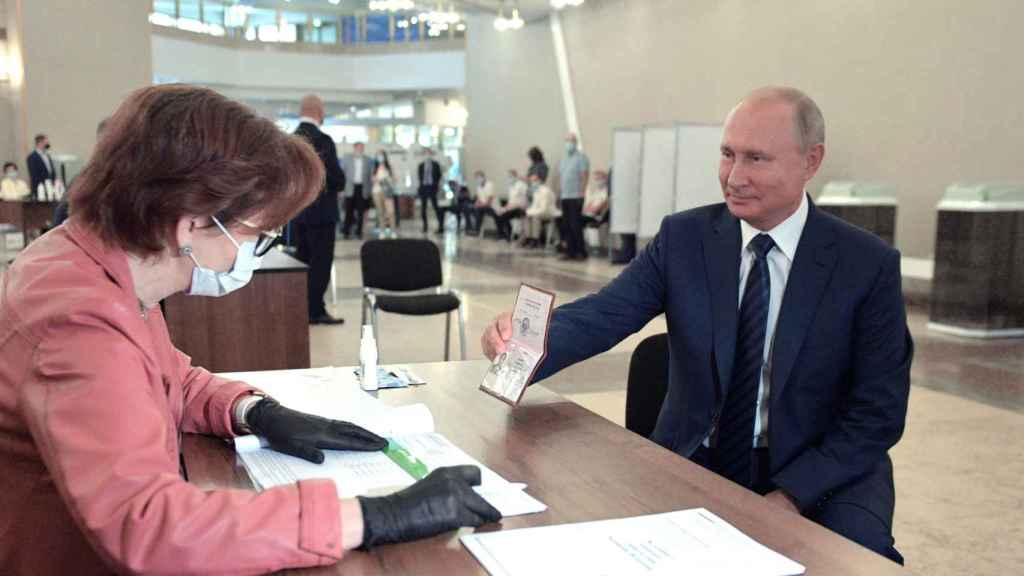 El presidente ruso, Vladimir Putin, muestra su pasaporte al acudir a votar en el referéndum.