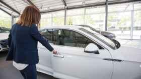Una mujer abre la puerta de un coche en un concesionario.