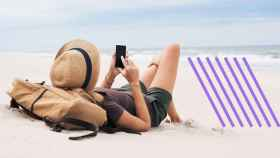 Una chica en la playa con su teléfono.