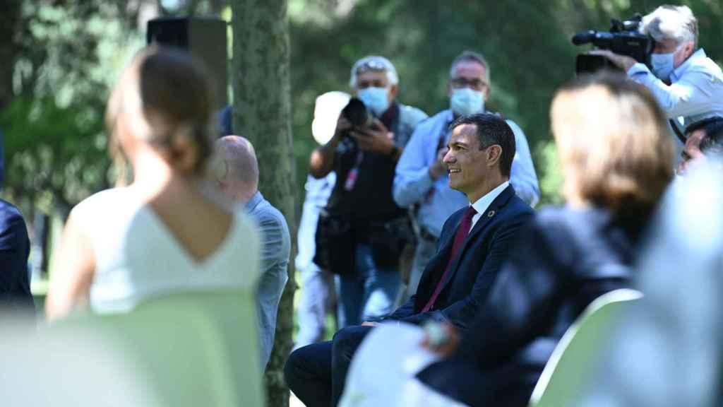Pedro Sánchez, en los jardines de Moncloa, y la ministra Yolanda Díaz desenfocada y de espaldas.