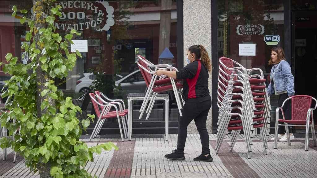 Una camarera prepara la terraza de una Cervecería 100 Montaditos.