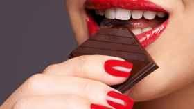 Una mujer, comiendo chocolate.