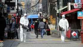 Un operario desinfecta una calle del barrio de Itaewon, en Seúl. Reuters