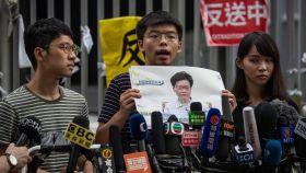 Los activistas en favor de la democracia Nathan Law (izqda), Joshua Wong (centro) y Agnes Chow (dcha) en rueda de prensa frente al edificio del Consejo Legislativo en Hong Kong.